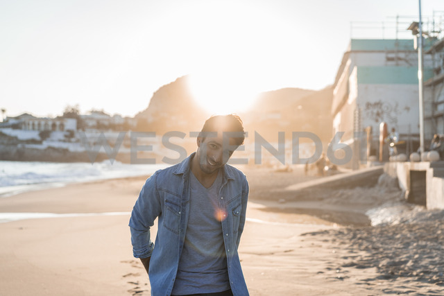 Portrait of smiling young man on the beach at sunset - AFVF00147