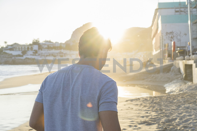 Back view of young man on the beach at sunset - AFVF00150
