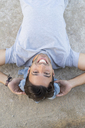 Portrait of laughing young man lying on a wall - AFVF00156
