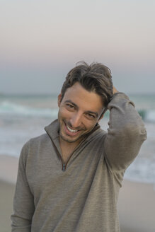 Portrait of smiling young man on the beach at twilight - AFVF00162