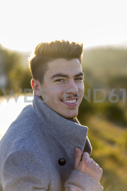Portrait of smiling young man at twilight - AFVF00165