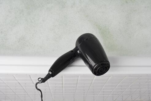 A hair dryer balancing on the edge of a full bathtub - FSIF02641