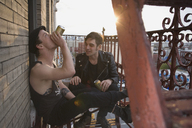 Two young men sitting on a fire escape drinking beer - FSIF02656
