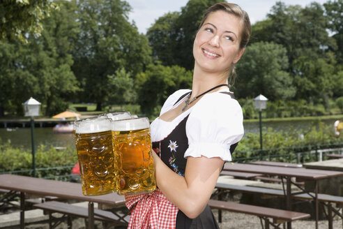 A traditionally clothed German woman serving beer in a beer garden - FSIF02695