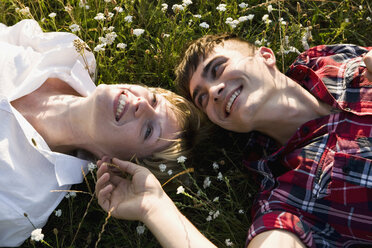 A young couple lying in on their backs in grass, close-up - FSIF02719