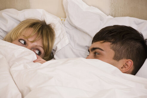 A young couple in bed with the duvet pulled up to their eyes - FSIF02728