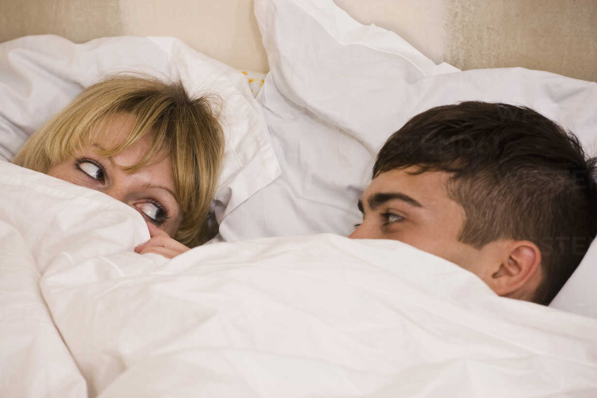 A young couple in bed with the duvet pulled up to their eyes - FSIF02728 - fStop/Westend61