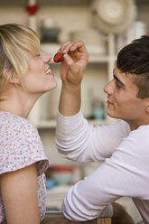 A young man holding a strawberry flirtatiously for a young woman - FSIF02740