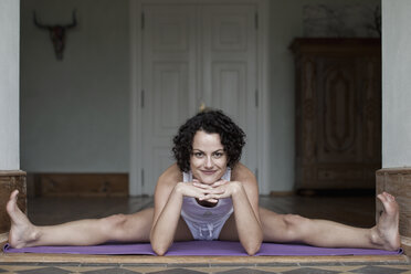 A woman doing the splits on a yoga mat - FSIF02749
