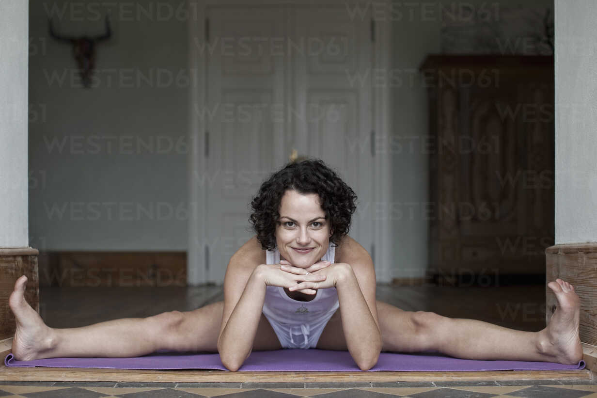 A woman doing the splits on a yoga mat - FSIF02749 - fStop/Westend61