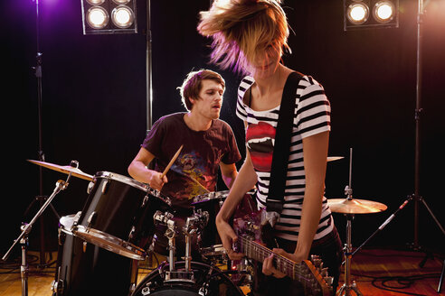 A man playing drums and a woman playing guitar in a rock band performing on stage - FSIF02758