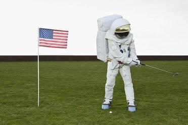 An astronaut swinging a golf club next to an American flag - FSIF02761