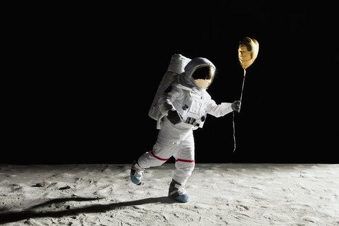 An astronaut on the moon holding a heart shaped helium balloon - FSIF02770