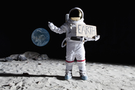 An astronaut on the moon with his thumb out, holding 'EARTH' sign - FSIF02773
