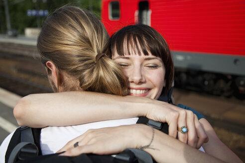 An happy woman hugs her boyfriend on a train platform - FSIF02788