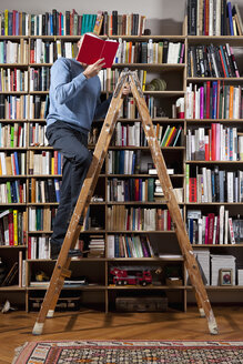 A man reading on a ladder in a home library - FSIF02838