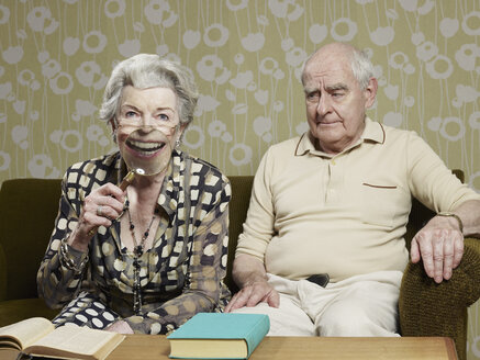 Senior man frowns as senior woman magnifies appearance of her mouth with magnifying glass - FSIF02886