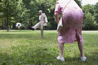 Senior couple play football in the park - FSIF02889
