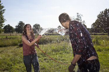 Girl sprays guy with hose on field - FSIF02892
