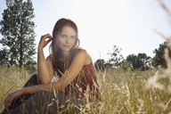 Girl sitting amongst timothy grass in the sunshine playing with her hair - FSIF02901