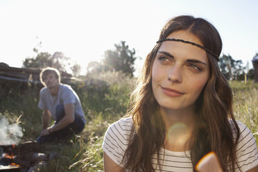 Profile of Long haired girl in field, and guy in the background looking at her - FSIF02904