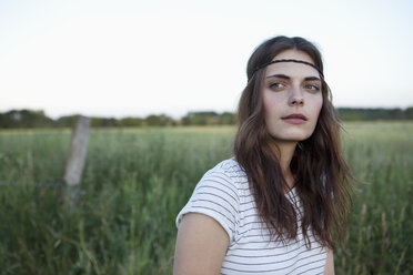 Profile of girl with hair band standing in field looking to the side - FSIF02910
