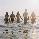 Five friends holding hands in a row while wading in the sea - FSIF02940