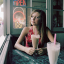 A teenage girl sitting at a table with a milkshake - FSIF02949