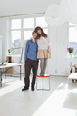A young women standing on a stool next to her tall boyfriend - FSIF02958