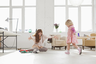 A young girl running towards her mother sitting on the floor - FSIF02967