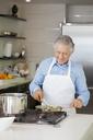 A senior man cooking vegetables in a saute pan - FSIF02988