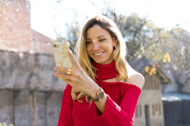 Portrait of smiling young woman looking at smartphone outdoors - AFVF00180