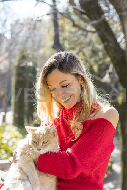 Happy young woman holding a cat in a garden - AFVF00183
