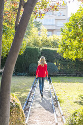 Young woman walking on path in a garden - AFVF00186
