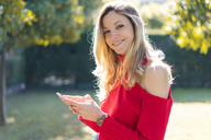 Portrait of smiling young woman using smartphone in a garden - AFVF00189