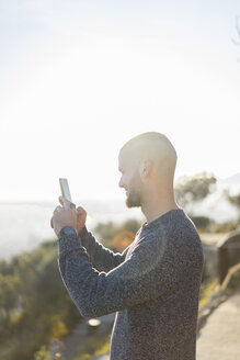 Smiling young man holding cell phone in backlight - AFVF00197