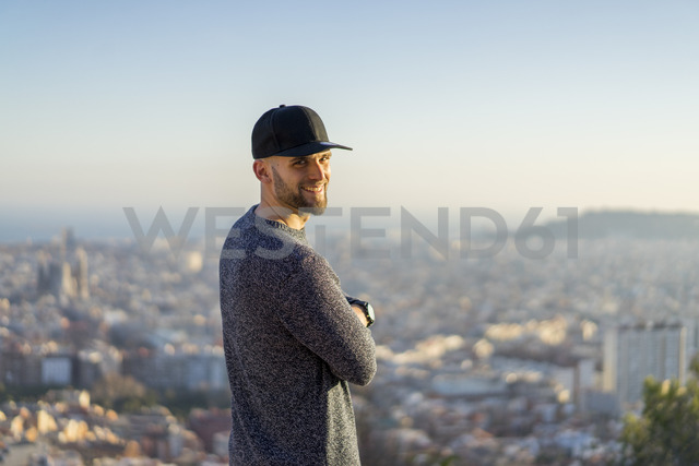 Spain, Barcelona, smiling young man standing on a hill overlooking the city - AFVF00203