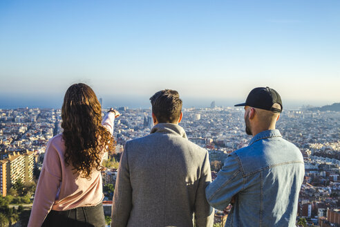 Spain, Barcelona, three friends on a hill overlooking the city - AFVF00215