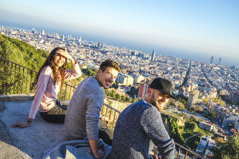 Spain, Barcelona, three smiling friends sitting on a wall overlooking the city - AFVF00218