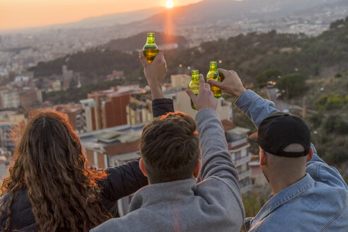 Spain, Barcelona, three friends with beer bottles on a hill overlooking the city at sunset - AFVF00221