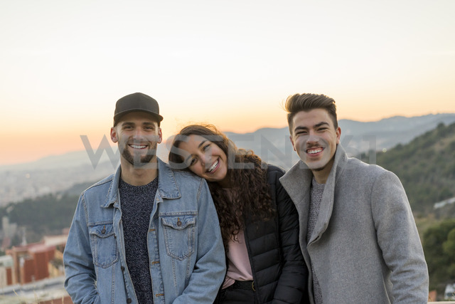 Portrait of three happy friends on a hill at sunset - AFVF00224