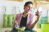 Young businesswoman having healthy lunch and using cell phone - WPEF00129