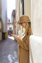 Fashionable young woman in a lane using cell phone - AFVF00230