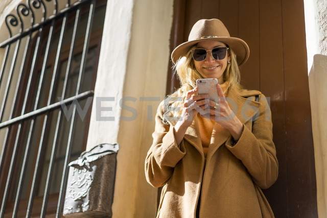 Fashionable young woman at house entrance using cell phone - AFVF00233