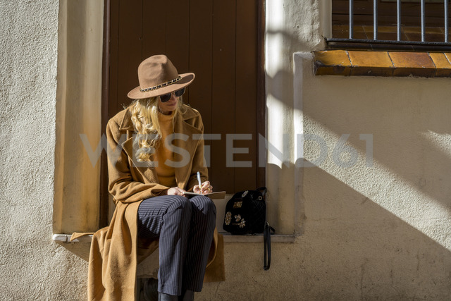 Fashionable young woman sitting at house entrance writing in notebook - AFVF00239