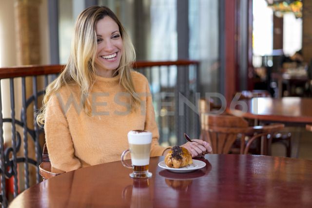 Happy young woman in a cafe enjoying pastry and coffee - AFVF00242