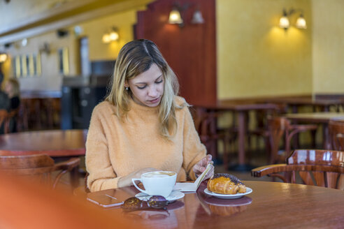 Young woman in a cafe with notebook, pastry and coffee - AFVF00245