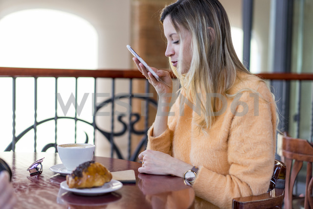 Smiling young woman in a cafe using cell phone - AFVF00248 - VITTA GALLERY/Westend61