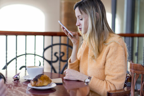 Smiling young woman in a cafe using cell phone - AFVF00248