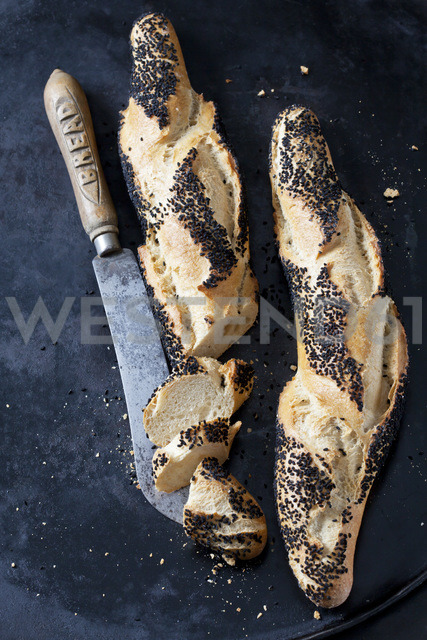 Two baguettes with black cumin and a bread knife on dark metal - CSF28963